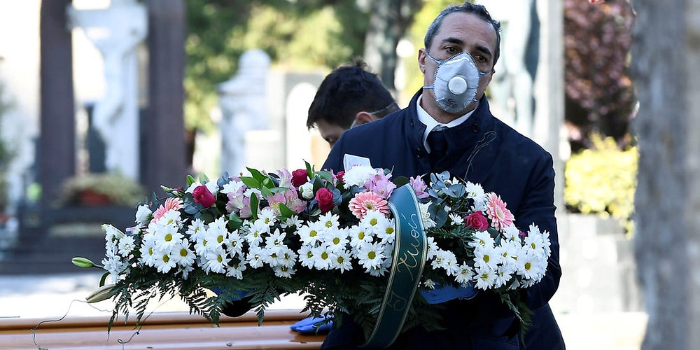 A northern Italian funeral home worker holds flowers for a funeral. The worker wears a mask and gloves.