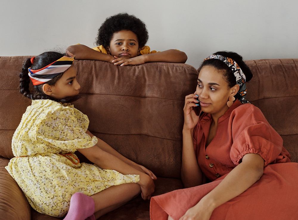 A mother with a phone to her ear and blue fingernail polish sits on a sofa with two young children.