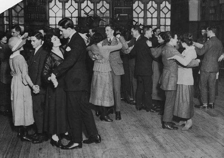 Historical photo from the 1920s USA showing couples on a wooden dancefloor all dancing very close together at a cuddle party.