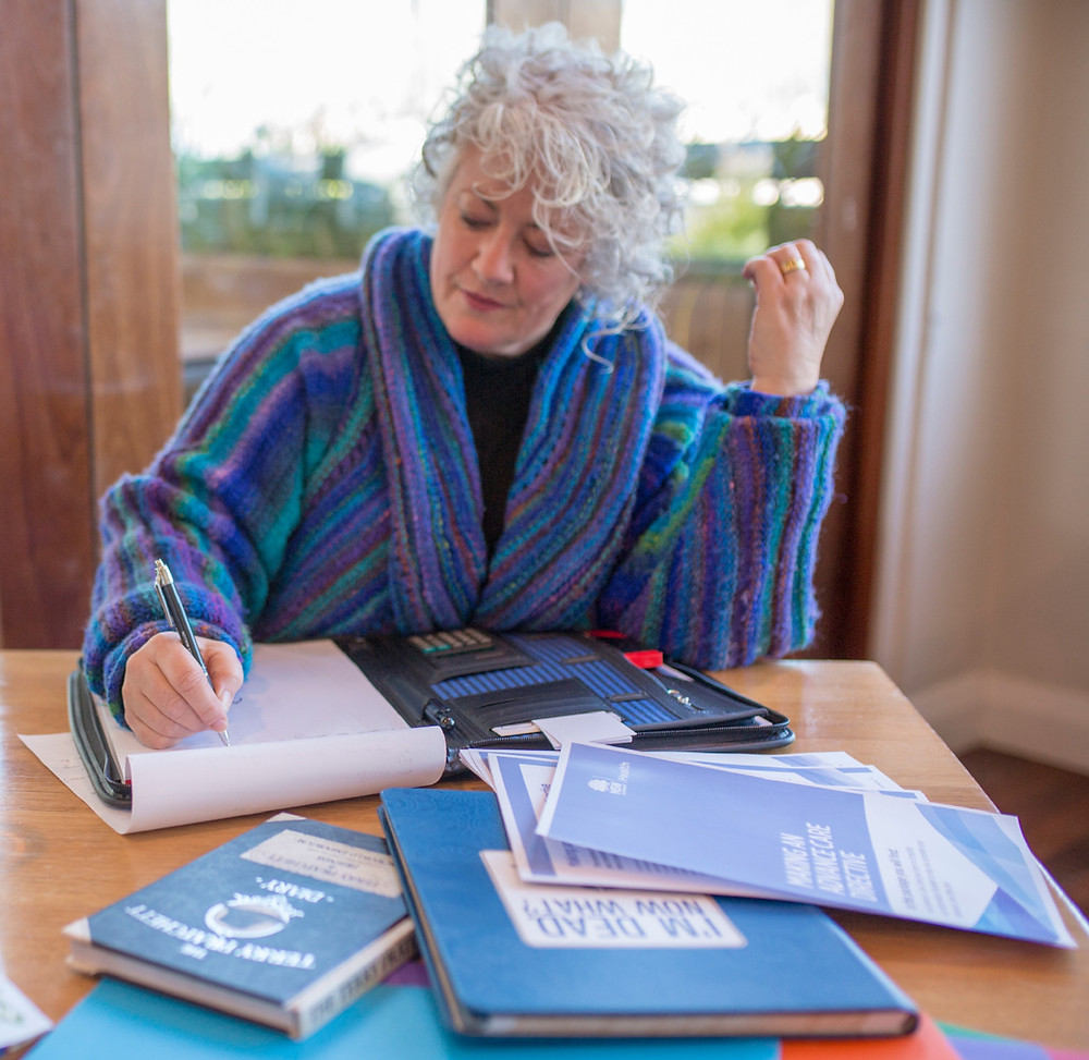 This is a picture of Annetta Mallon, a woman with white curly hair. Annetta is sitting at a wooden table writing with end of life books and papers around her.