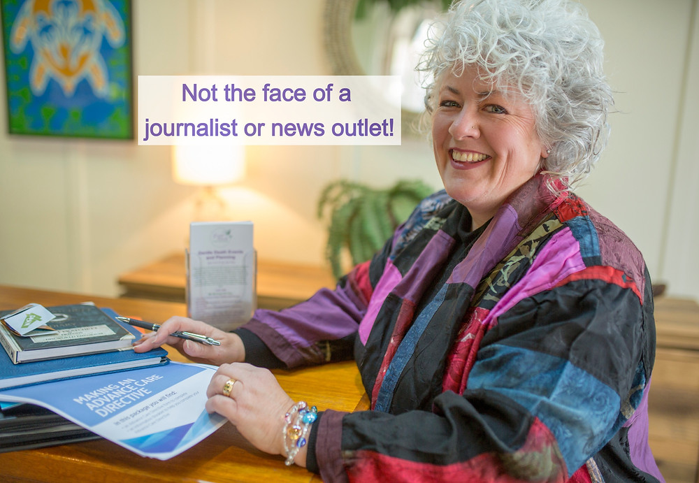 "A picture of Dr Annetta Mallon, a woman with white curly hair, a big smile and a colourful jacket. She is standing in front of a high table with end of life paperwork stacked up. The words ""Not the face of a journalist or news outlet!"" is in the image."
