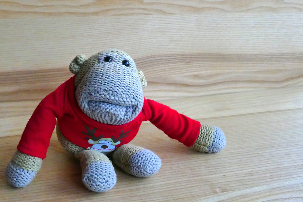 A grey knitted monkey with a red jumper is looking at the camera.
