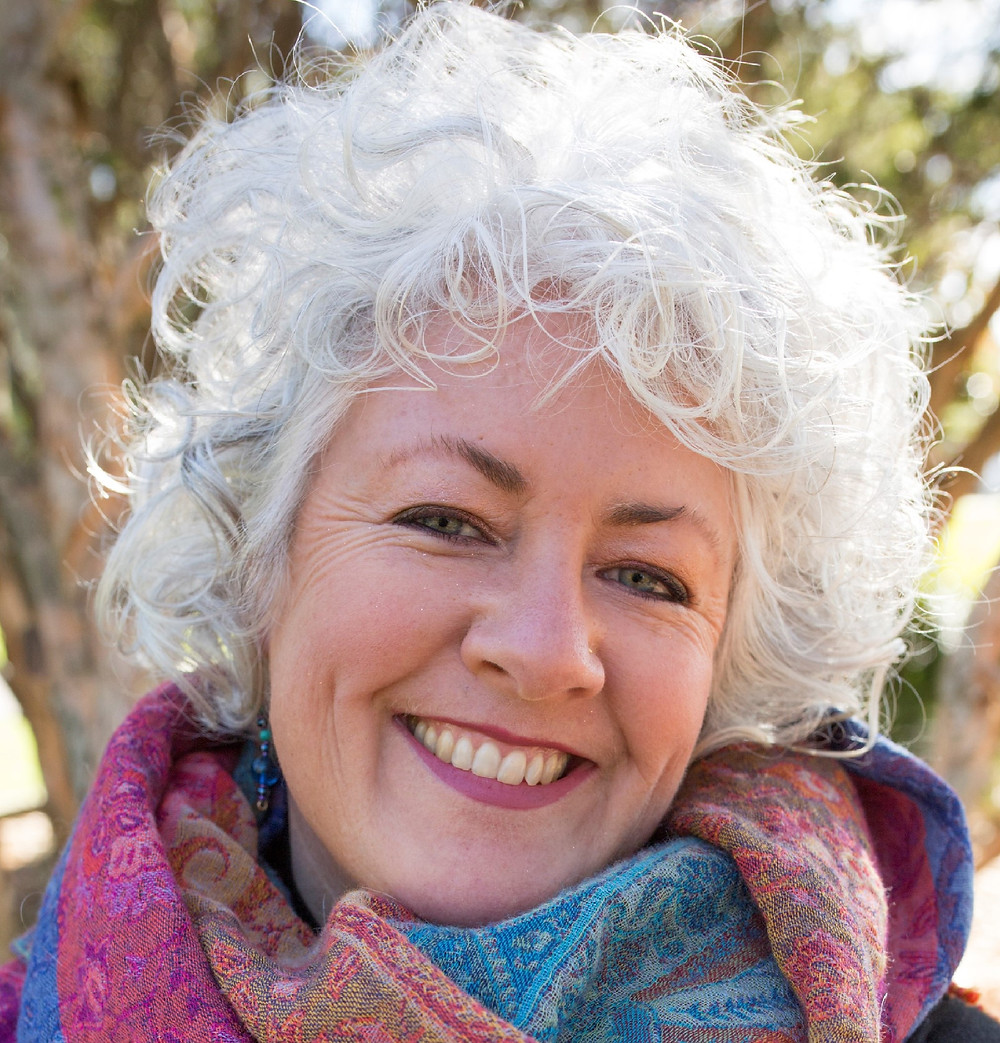 A headshot of Dr Annetta Mallon, a woman with curly white hair, a big smile, and a multicoloured scarf around her neck.