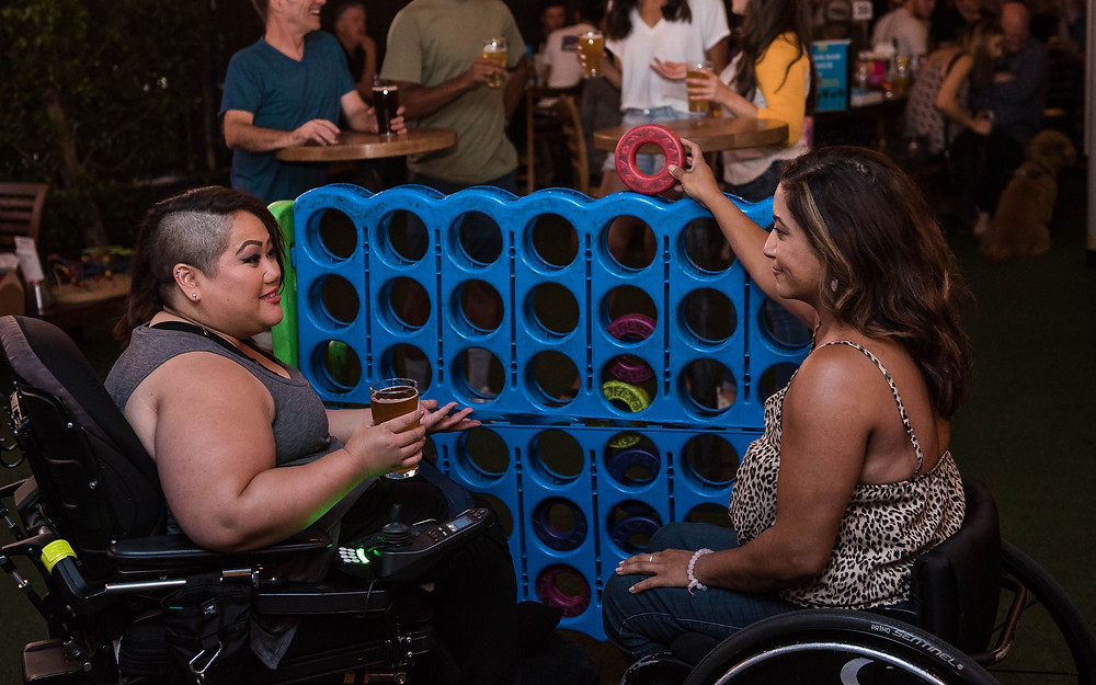 Two women in wheelchairs are playing a giant game of Connect 4. One woman holds a beer while the other holds a game piece.