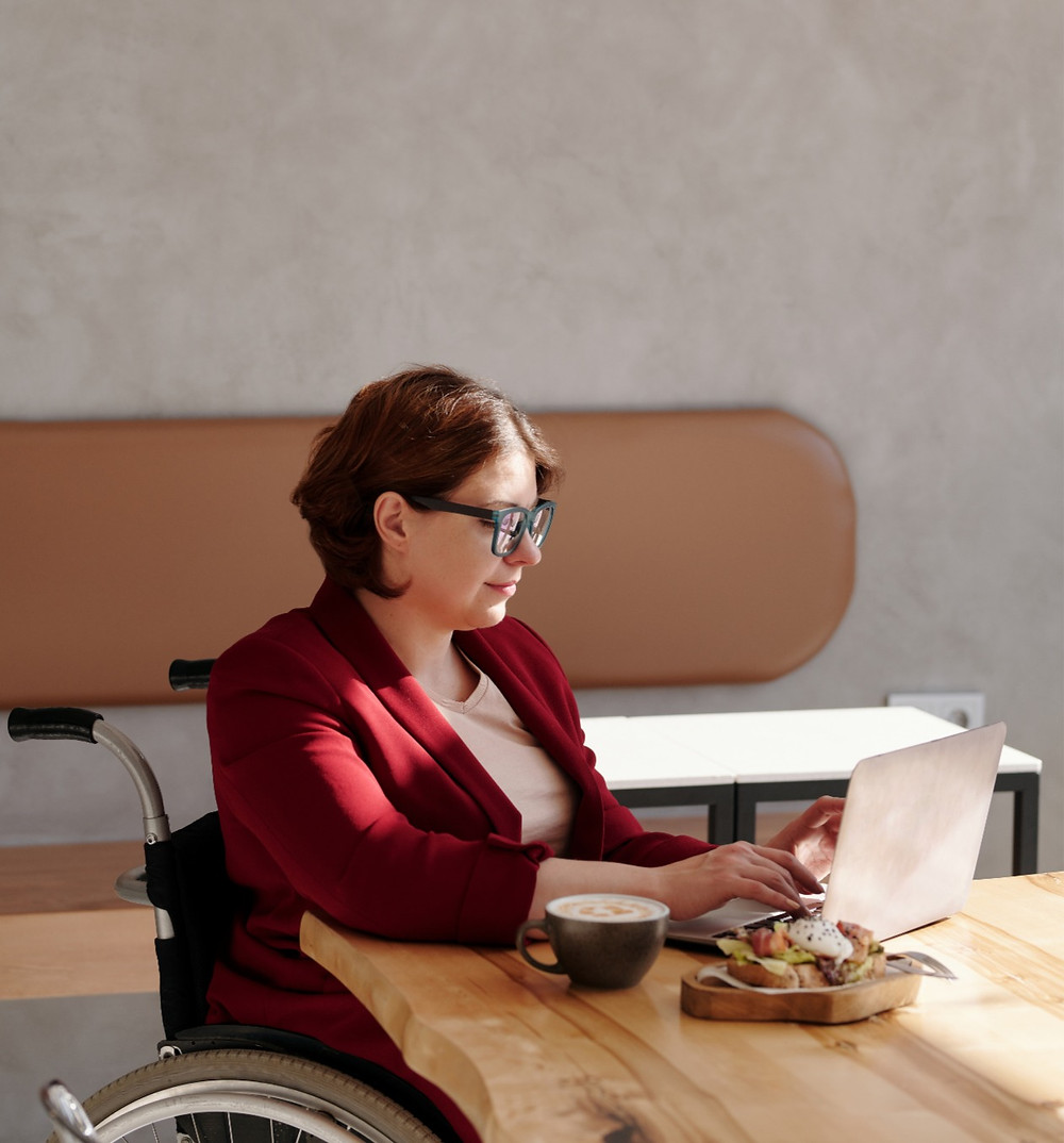 A woman in a cranberry red jacket with black framed glasses sits in her wheelchair at a natural-edge table. She has a small laptop, a coffee and a croissant on a board in front of her. She has the sun on her face.