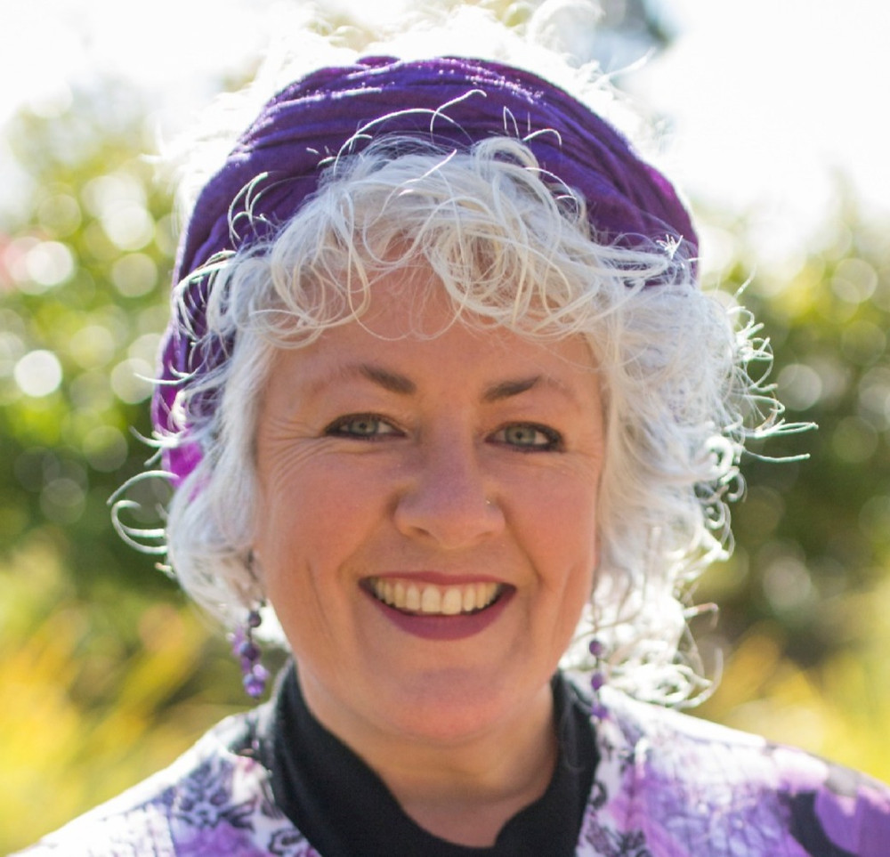 A picture of Annetta Mallon, a woman with a big smile, white curly hair and a purple scarf wrapped around her head.