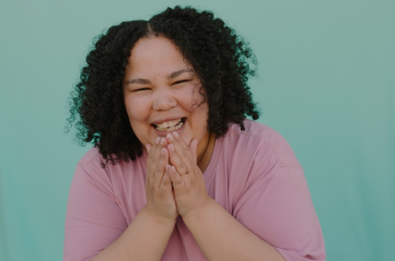 A woman with a big smile and black natural curly hair laughs into the camera. She is wearing a pink t-shirt and her hands are clapping together in front of her chin.