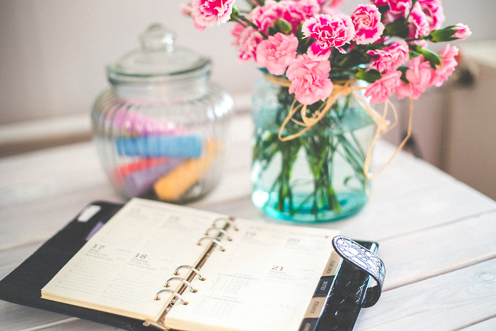 A week by week diary planner sits open on a desk with a vase of pink carnations and a glass jar with coloured chalk sticks.