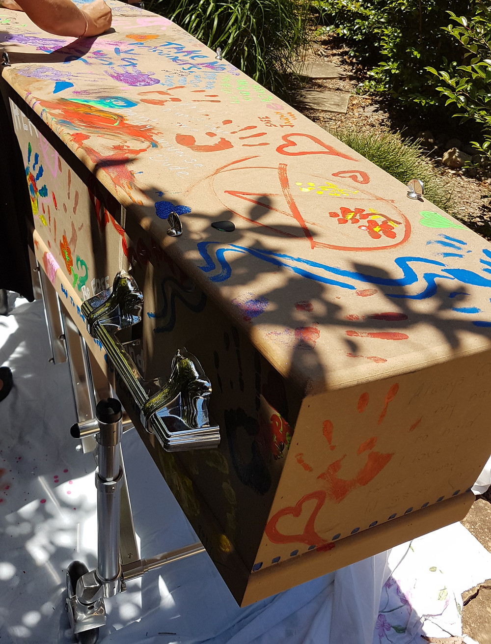 Cardboard coffin being painted.