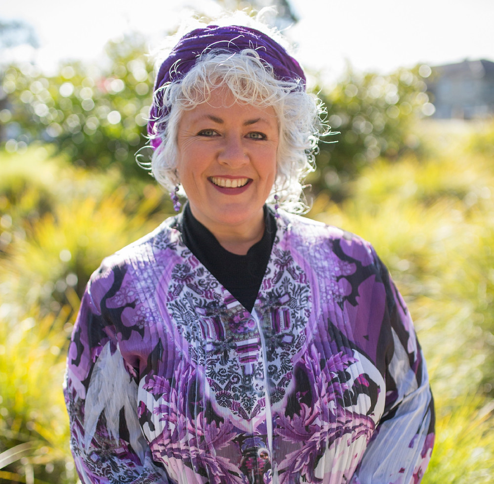 Dr Annetta Mallon has white curly hair and a big smile. Annetta is looking into the camera with the sun behind her, wearing a purple scarf wrapped around her head.
