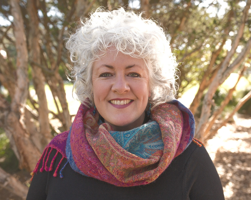 This is a picture of Dr Annetta Mallon. Annetta is a woman with a big smile, white curly hair and a colourful scarf around her neck.