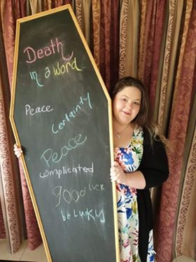 """Owner of You n' Taboo, Rebecca Lyons, stands behind her bespoke casket lid blackboard. Rebecca wears a floral dress with her dark hair worn long, and there are death-positive words written in coloured chalk on the coffin lid. Words include """"Death in a word"""", peace, certainty."""