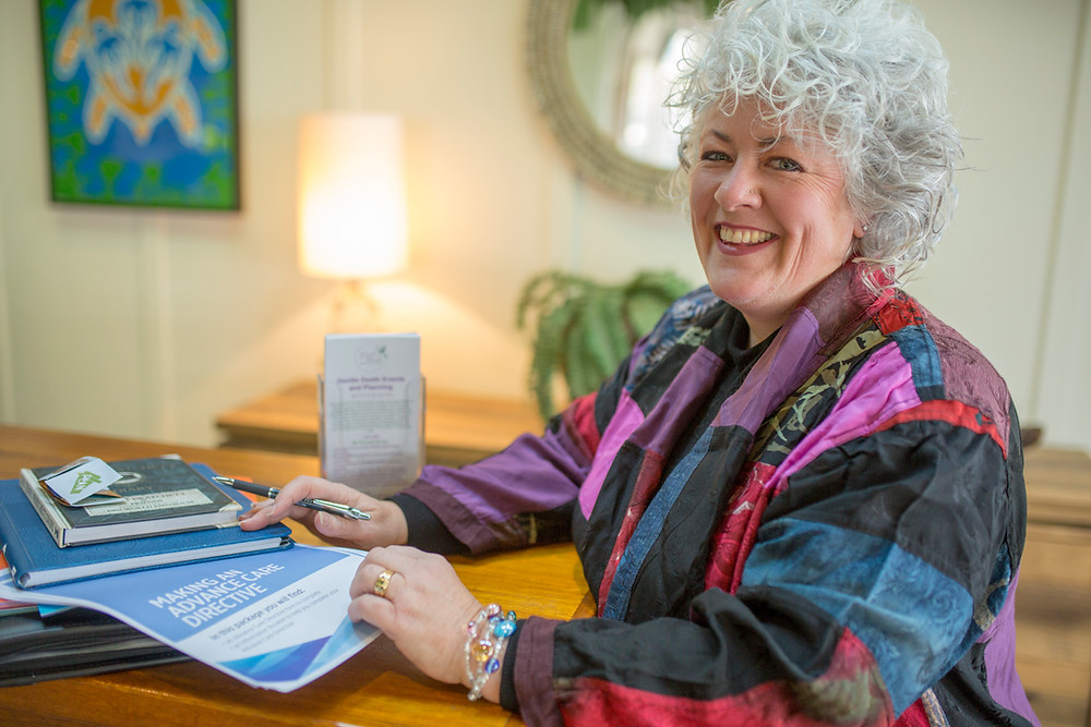 Dr Annetta Mallon is a white haired End of Life Consultant. She is seated with advance care directive paperwork, smiling at the camera.