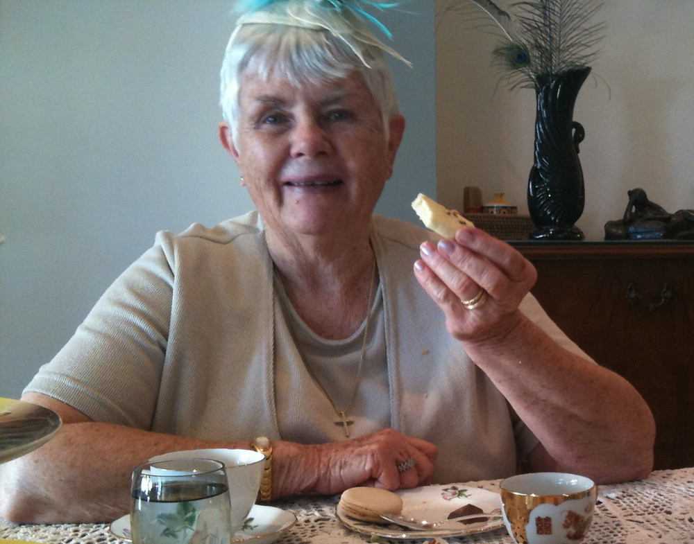 A happy woman with short white hair and a pale blue fascinator on her head sits in front of a high tea table. She is smiling and happy.