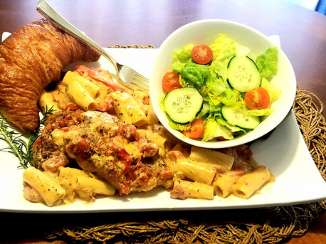 Boneless Pork Chops Alla Pizzaiola in a Garlic Roasted Tomato and Heavy Cream Sauce with Rigatoni Pasta, Side Salad and a Croissant.