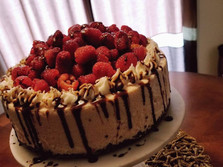 White Chocolate Raspberry Cheesecake with a Chocolate drizzle sitting on a scrumptious Chocolate Butter Crust.