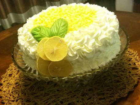 Luscious Lemon Cake adorned with fresh lemon slices and Basil Leaves