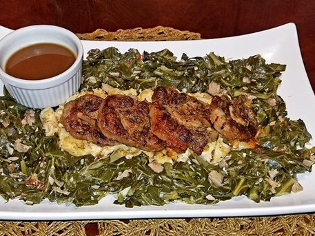 Oven Braised Oxtails sitting on a bed of Three Cheese Macaroni topped with Toasted Bread Crumbs, surrounded by Seasoned Collards with Diced Smoked Turkey Meat and a side of Au Jus Gravy.