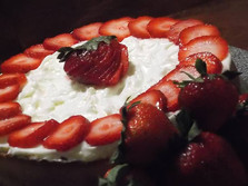 New York Style Cheesecake sitting atop a scrumptious Butter Crust adorned with fresh cut Strawberries finished with a Cream Cheese Whipped topping.