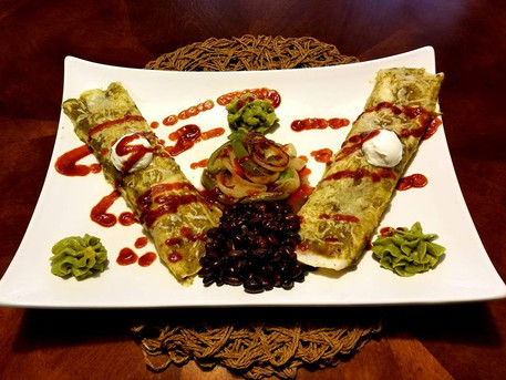 Beef Enchiladas with a      Green Chile Sauce, Grilled      Peppers and Onions,      Black Beans, Avocado      Mash, and a dollop of Sour      Cream finished with a      Sriracha drizzle.