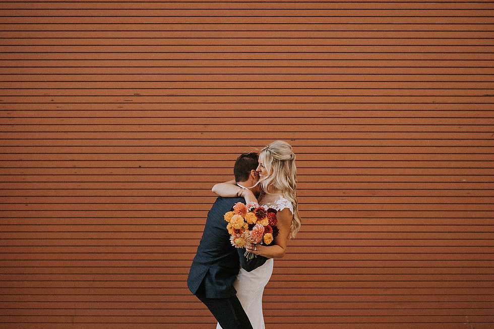 Bride and groom in front of orange backdrop
