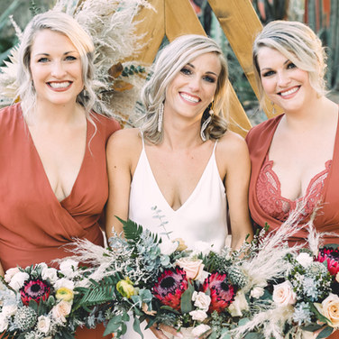two bridesmaids with flowers and smiling bride