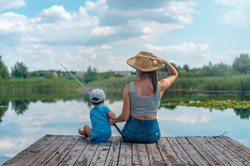 woman-and-boy-sitting-on-dock-holding-fi