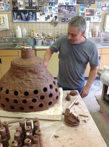 Albert Pfarr working on a complicated ceramic scultpure.