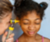 A young girl getting her ear examined, representing the mobile health services provided by the audiologists at High Level Speech & Hearing Center in New Orleans, LA