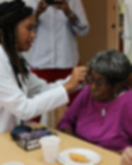 A specialist inserting a hearing aid representing community work done by speech pathologist High Level Speech & Hearing Center in Harahan, LA