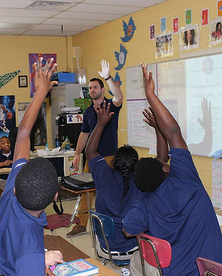 Classroom of kids raising their hands representing a donation made by audiology clinic High Level Speech & Hearing Center in New Orleans, LA