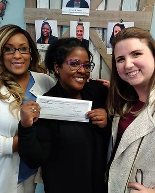 Three women smiling with a check representing a $10,000 donation to The Beautiful Foundation to Help Young Girls donated by speech therapist High Level Speech & Hearing Center in New Orleans, LA