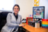 A professional smiling at her desk in the office of speech therapist High Level Speech & Hearing Center in Harahan, LA