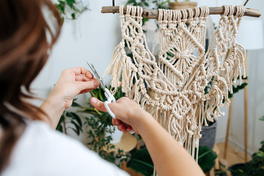 Close-up picture, girl cuts off scissors ropes, weaves a beautiful pattern of macrame.jpg