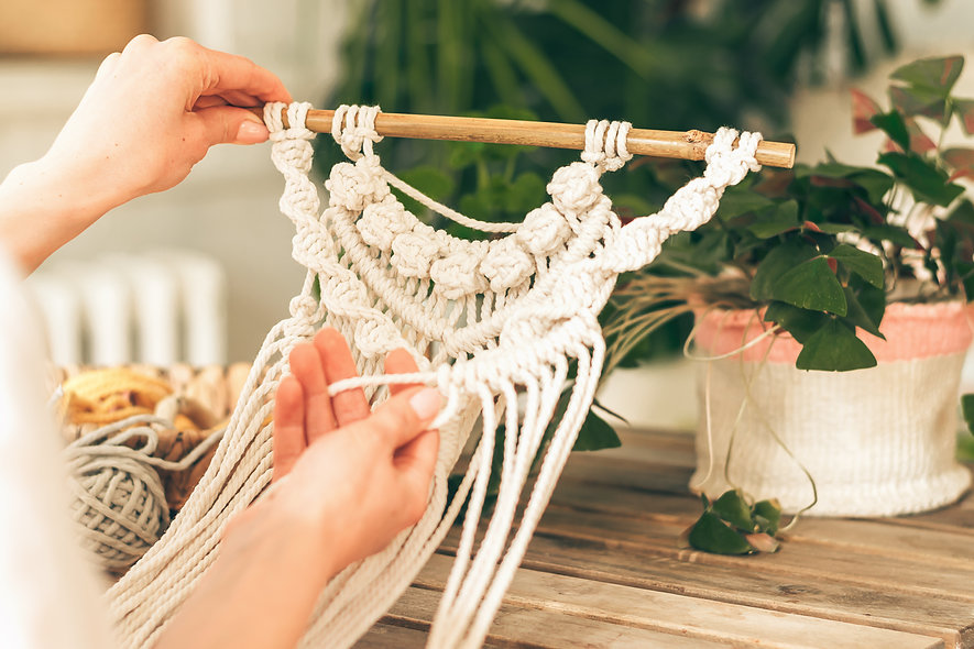 Close up of women's hands weaving macrame in a home workshop.Home decor.Handmade concept.S