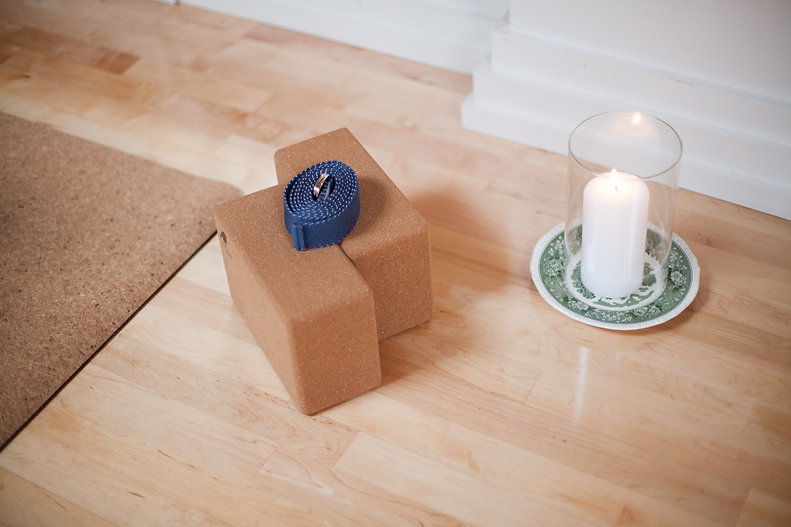 Close up photo of two Yoga Blocks, a Yoga strap, and a candle
