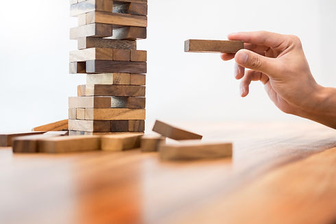 Business man placing wooden block on a t
