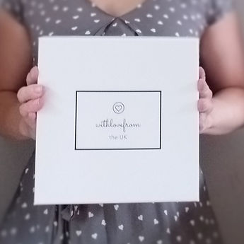 Woman holdin a white glossy box with withlovefromtheuk logo on lid