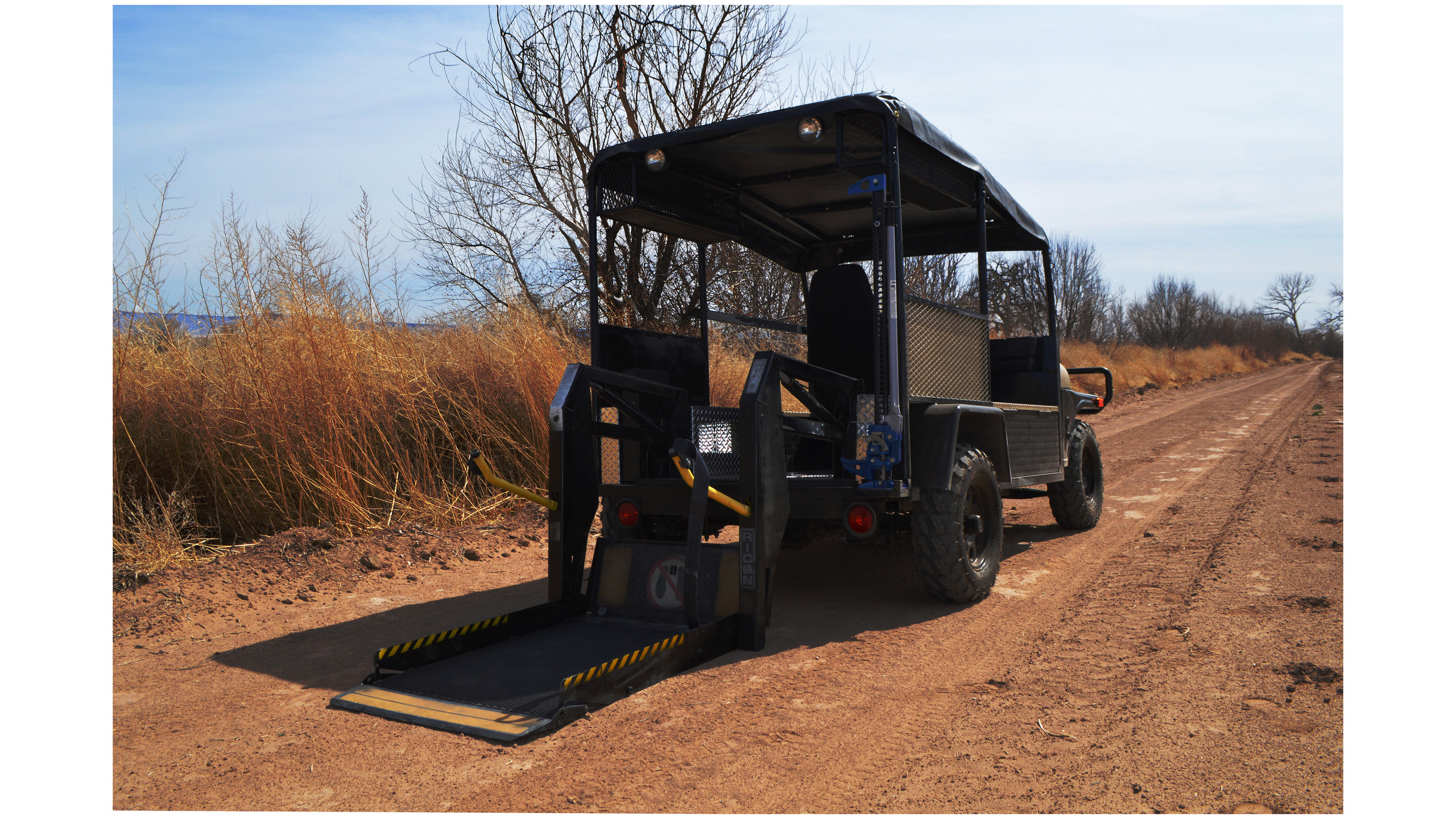2018 Buddy Buggy UTV with wheelchair lift extended on dirt trail