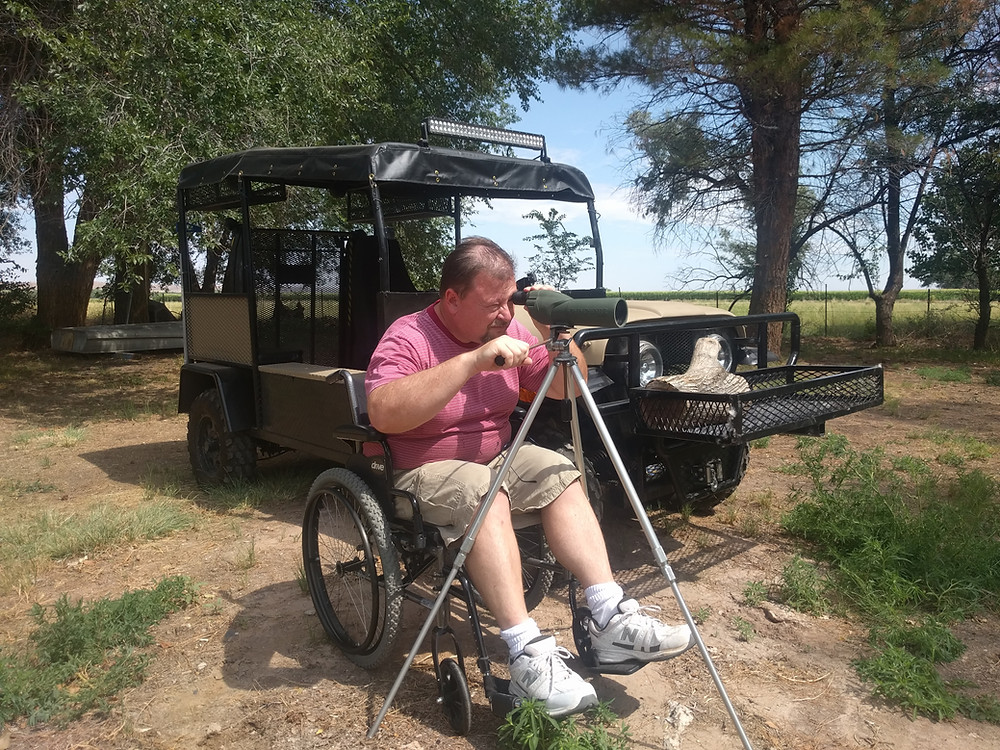Man sitting in a wheelchair looking through telescope next to a Buddy Buggy UTV.