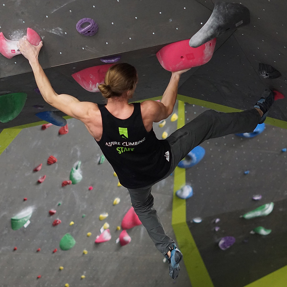 Kid climbing a green wall with black holds.