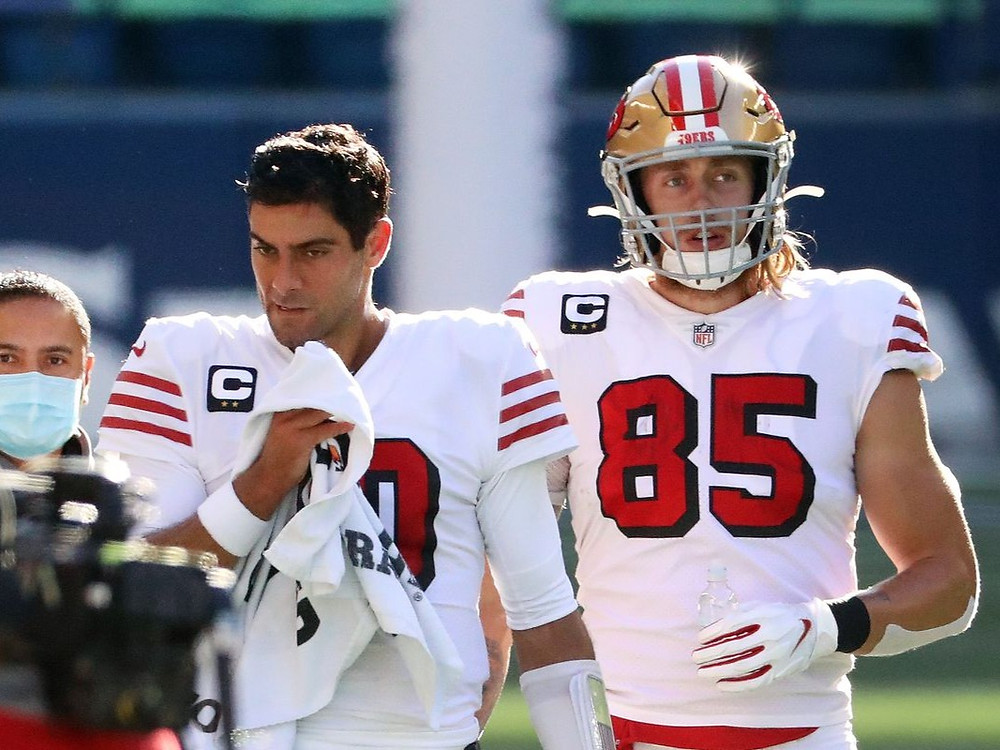 NFL quarterback Jimmy Garoppolo and tight end George Kittle of the San Francisco 49ers walk along the sideline during a 2020 NFL season game