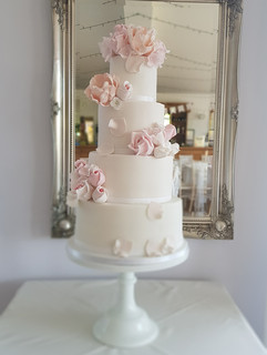 Pretty 4 tier wedding cake with roses and petals