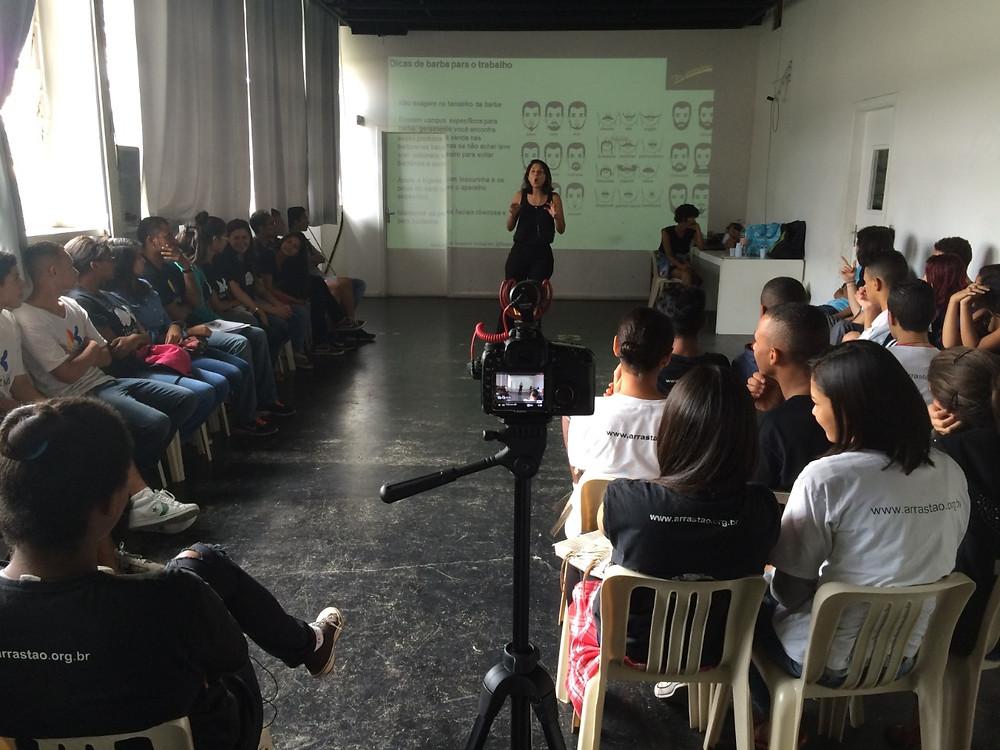 Flávia Apolinário em frente a uma sala repleta de alunos palestrando sobre o tema auto-imagem no ambiente de trabalho