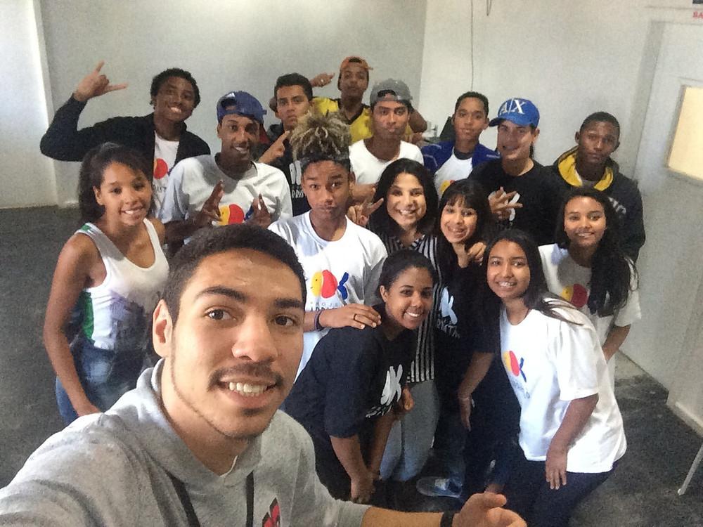 Imagem com Flávia Apolinário reunida entre jovens de 13 a 18 anos, integrantes do Projeto Arrastão