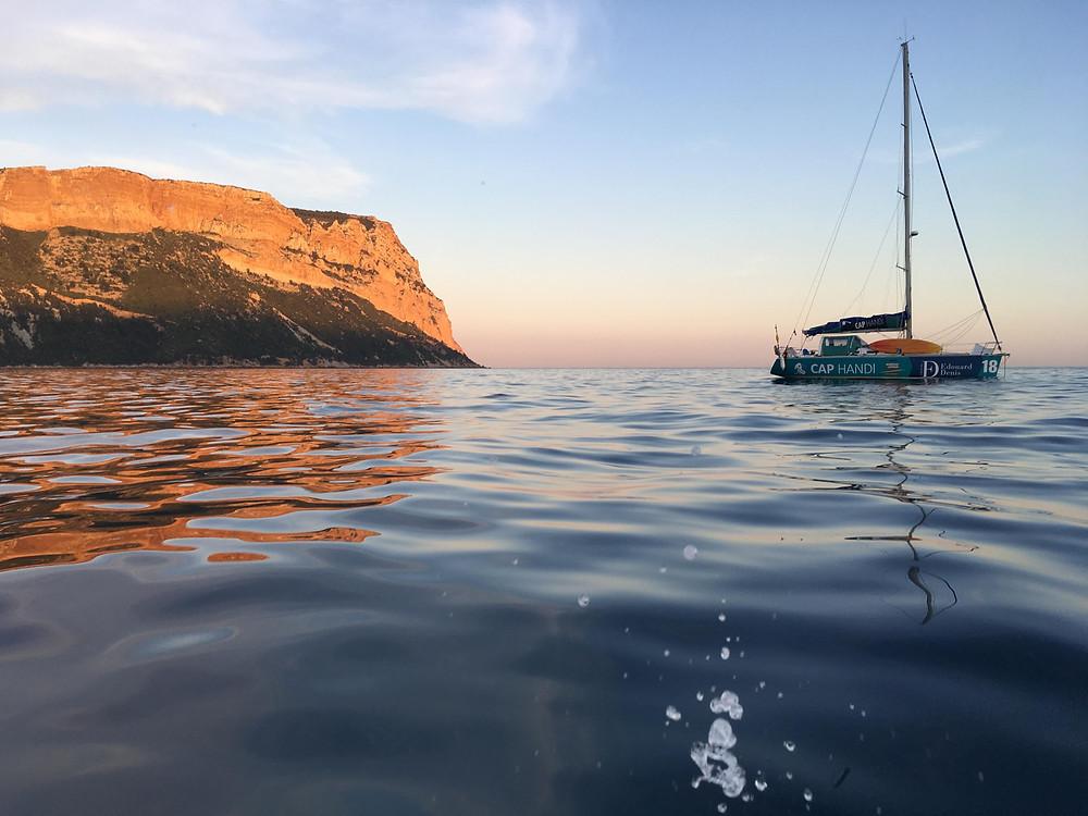 bateau cap handi au mouillage au large de Cassis, couché de soleil