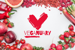 Veganuary with a love heart in the middle shaped as a V, surrounded by red fruits and vegetables as a bored