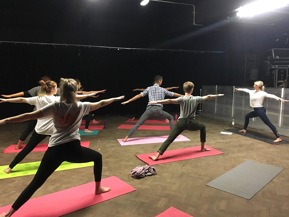 A group of students wearing active gear and standing on yoga matts, perform the warrior pose