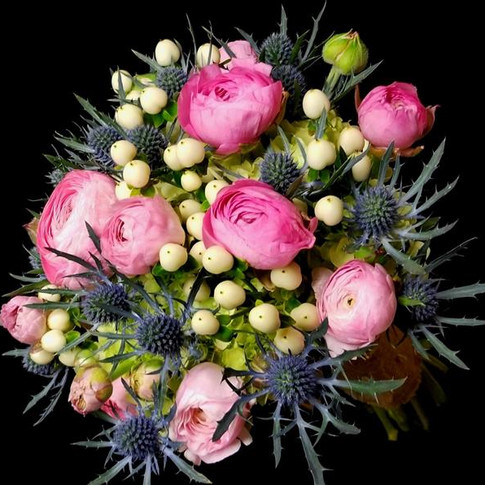 rustic bouquet featuring pink ranunculi, eryngium blossoms, ivory hypericum berries, green hydrangeas