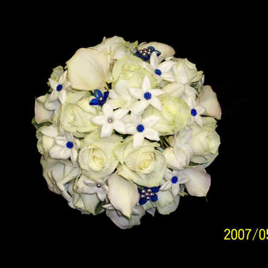white bouquet featuring roses, stephanotises, mini calla lilies, blue gems